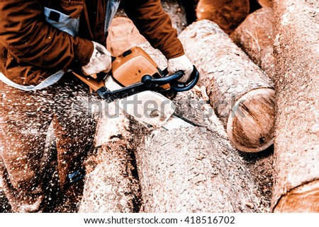 Man sawing a log in his back yard with orange saw - stock photo