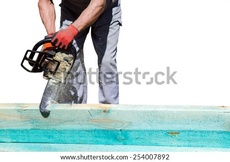 Man sawing a wooden beam with a chain saw - stock photo