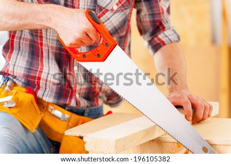 Man sawing. Close-up of handyman using saw in workshop