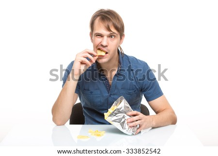 man scattered potato chips on the table - stock photo