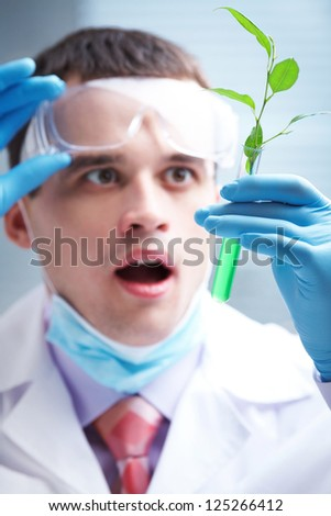 man scientist holding a test tube with plant