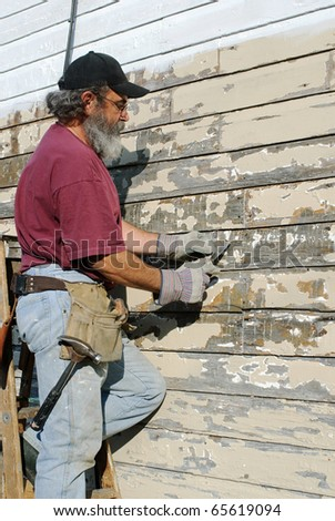 Man Scrapping Paint from House - stock photo