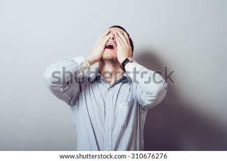 man screaming mouth open, keep your head arm, wearing a casual blue shirt, isolated gray background, the concept of facial emotions - stock photo