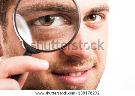 Man searching for something using a magnifying glass - stock photo