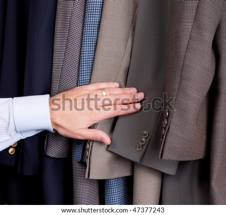 Man searching through suits - stock photo