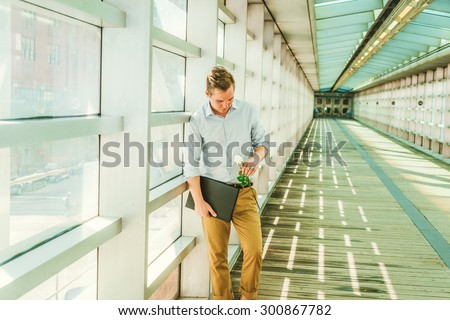 Man seeking love in New York. Wearing white shirt, yellow pants, carrying laptop computer, a young guy standing on walk way on campus, looking down at white rose on hand, missing you. Instagram effect - stock photo
