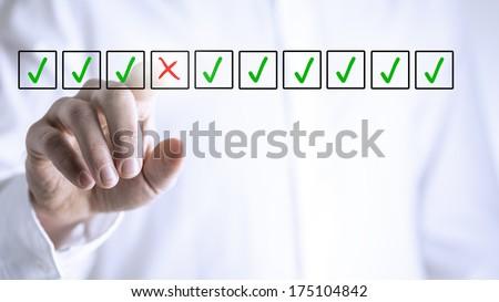 Man selecting a red cross in a box from a line of green check marks or ticks in boxes on a virtual screen conceptual of individuality, quality, failure and negativity - stock photo