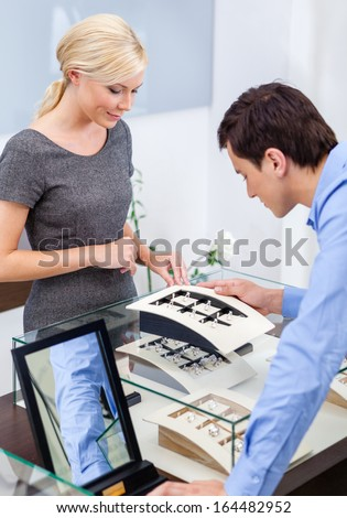 Man selecting engagement ring at jeweler's shop. Concept of wealth and luxurious life