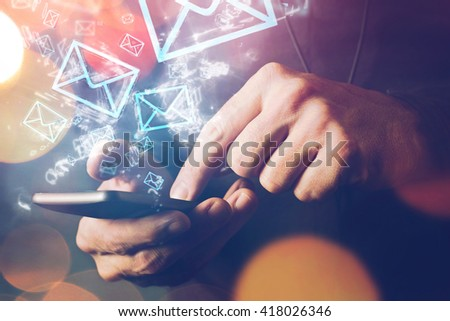 Man sending e-mail message to mailing list contacts using smartphone, close up of hands holding phone. - stock photo