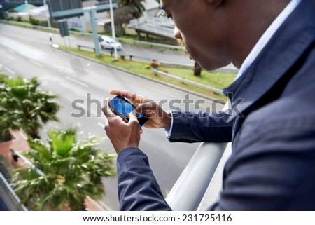 Man sending text message on cell phone in city overpass bridge - stock photo