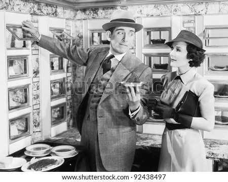 Man serving a dish to a woman in an Automat - stock photo