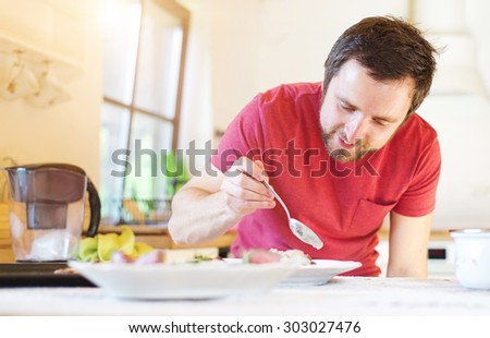 Man serving grilled beef steak, asparagus and baked potatoes