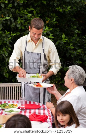 Man serving his mother at the table - stock photo