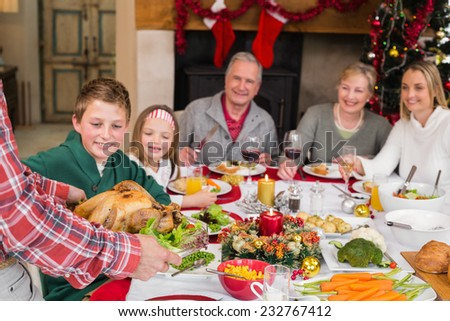 Man serving roast turkey at christmas at home in the living room - stock photo