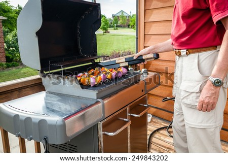 Man set shish kebob skewers on a grill - stock photo