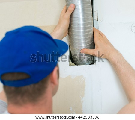 Man setting up ventilation system indoors.
