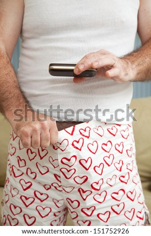 "Man sexting a picture of his ""weiner"", or penis with his cellphone.   - stock photo"
