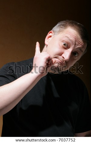 Man shake one's thumb at someone over dark background - stock photo