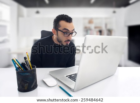 Man Shocked Reading Message on Computer in Office . - stock photo