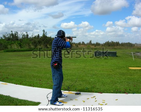 Man shooting trap targets at an outdoor shooting range - stock photo