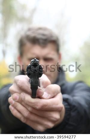 man shoots from pistol. Selective focus on pistol barrel. - stock photo