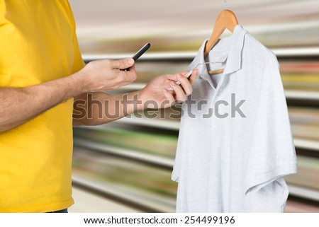 Man Shopping In Boutique Scanning The Price Tag With Mobile Phone - stock photo
