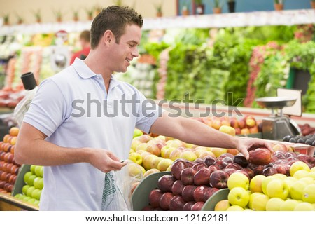 Man shopping in produce setion of supermarket - stock photo