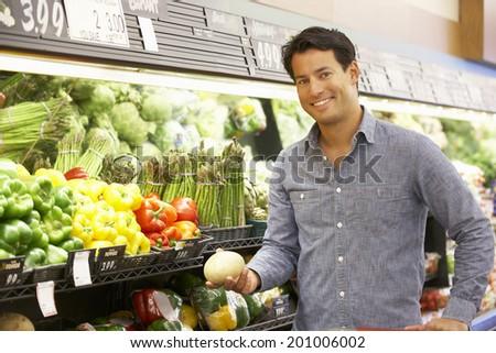 Man shopping in supermarket - stock photo