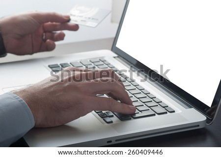 Man shopping online from his laptop computer with his credit card - stock photo