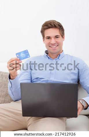 Man Shopping Online From Home Using Credit Card And Laptop - stock photo