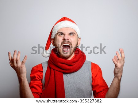 Man shouting in anger. Happy Businessman wearing a Santa hat on New Year's corporate parties. Studio photo, isolated on a gray background