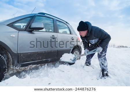 Man shoveling snow to free his stuck car - stock photo