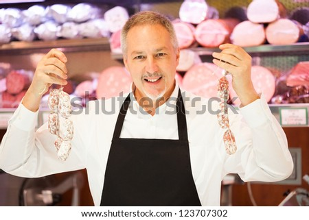 Man showing a salami in a grocery store - stock photo