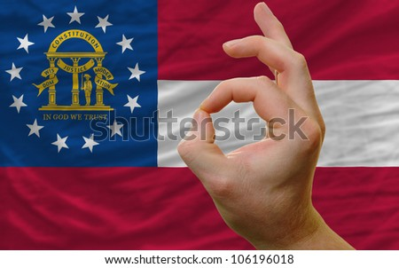 man showing excellence or ok gesture in front of complete wavy american state flag of georgia symbolizing best quality, positivity and success