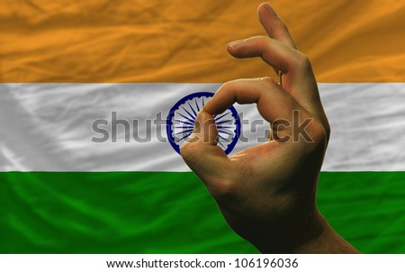 man showing excellence or ok gesture in front of complete wavy india national flag of  symbolizing best quality, positivity and success - stock photo