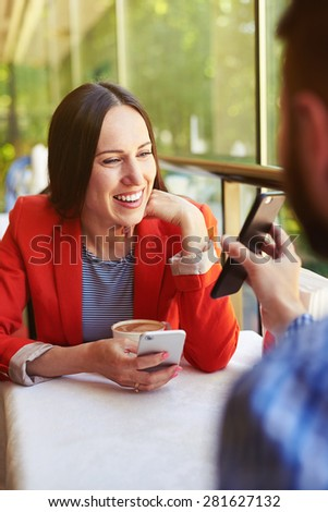 man showing his cellphone to smiley young woman. loving couple at the table in a cafe - stock photo