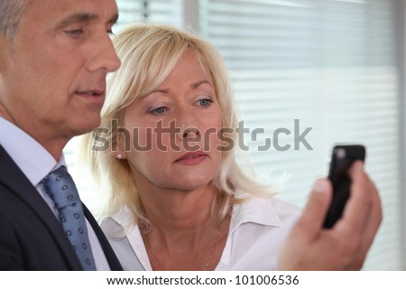 man showing mobile phone to woman - stock photo