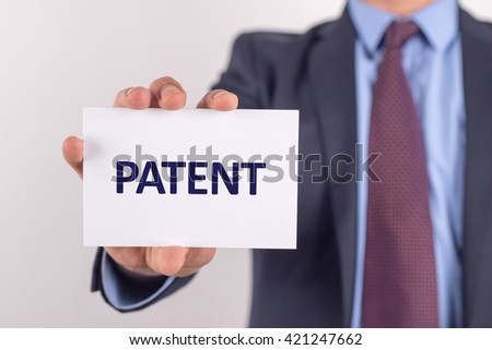 Man showing paper with PATENT text - stock photo