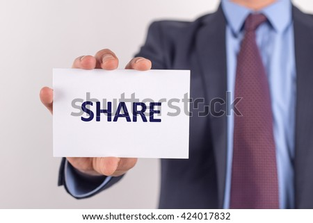 Man showing paper with SHARE text - stock photo
