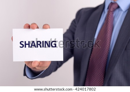 Man showing paper with SHARING text - stock photo