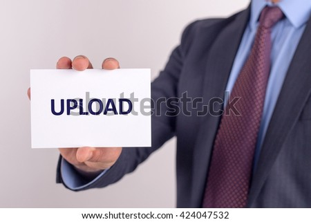 Man showing paper with UPLOAD text - stock photo