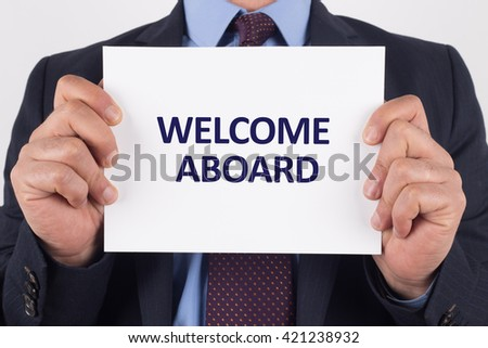 Man showing paper with WELCOME ABOARD text - stock photo