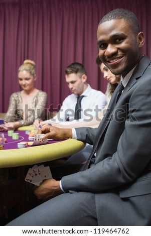 Man showing poker hand under table at casino