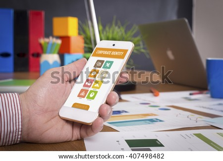 Man showing smartphone Corporate Identity on screen - stock photo