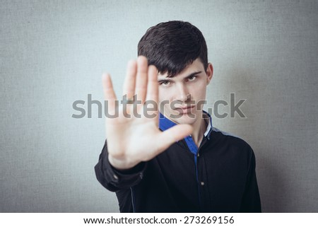 Man showing stop hand. Gesture. On a gray background. - stock photo