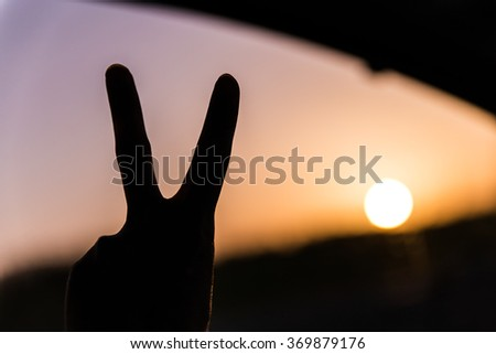 man showing the peace sign in front of a sunset - stock photo