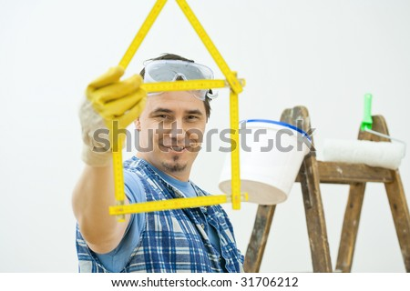 Man showing yellow folding ruler shaped in form of house. Isolated on white background. Selective focus on man. - stock photo