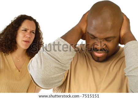 Man shutting his ears and not listening to the persistent yelling of his spouse - stock photo