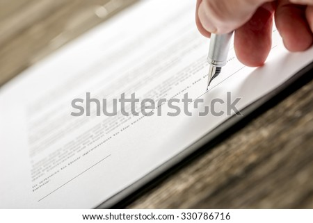 Man signing business document, application, subscription form  or insurance papers with silver pen on wooden desk. - stock photo