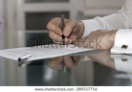 Man signs formal paper. Businessman hands working on paper document on glass office table making strong reflection with fountain pen stylish shirt with golden cuff link soft smothered background - stock photo